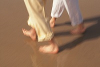 Photo of two people walking on the beach
